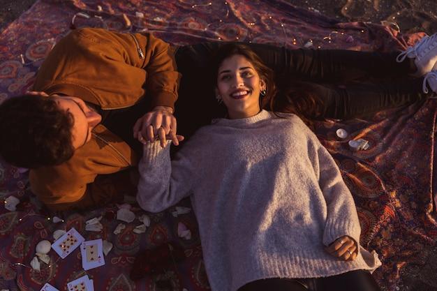 Happy couple lying on coverlet