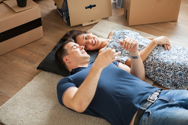 Coppia felice sdraiata sul pavimento dopo essersi trasferita. donna e uomo che sorridono