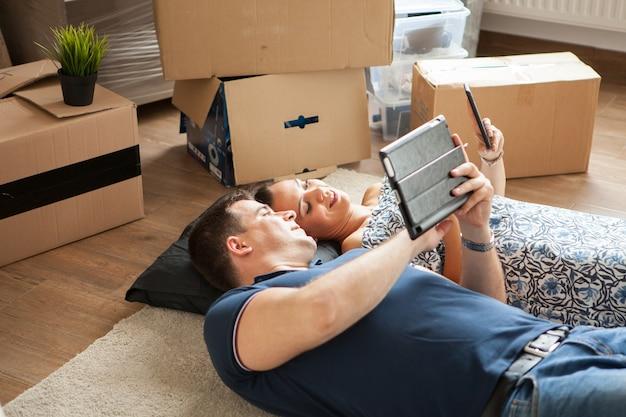 引っ越してから床に横たわる幸せなカップル。女性と男性の笑顔