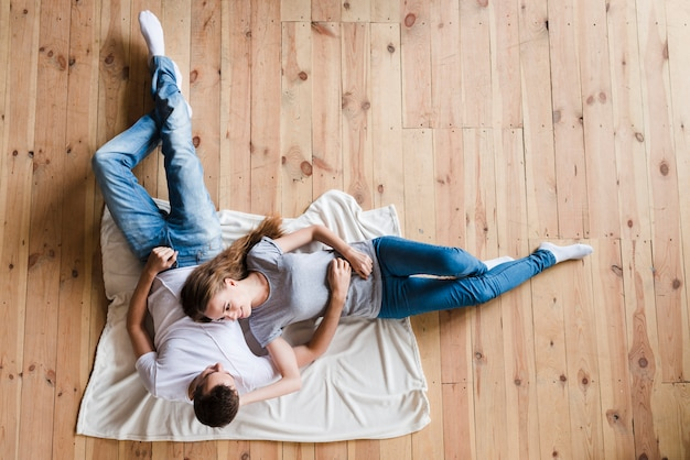 Happy couple lying on sheet on floor