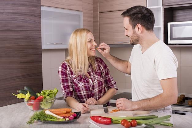 キッチンカウンターで野菜と新鮮なサラダを作る幸せなカップル