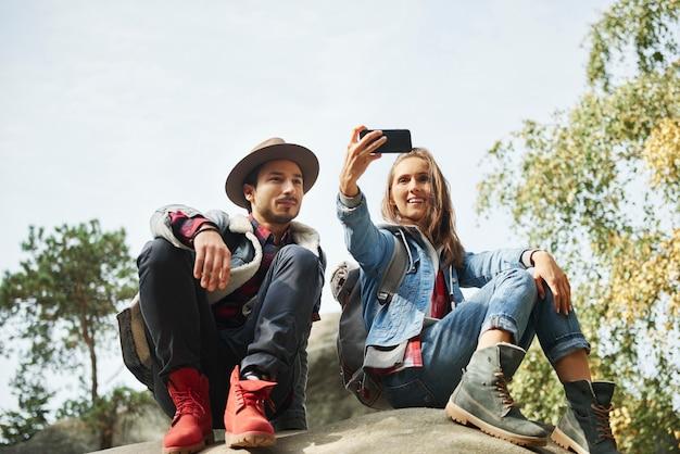 ハイキング旅行中に自分撮りを作る幸せなカップル