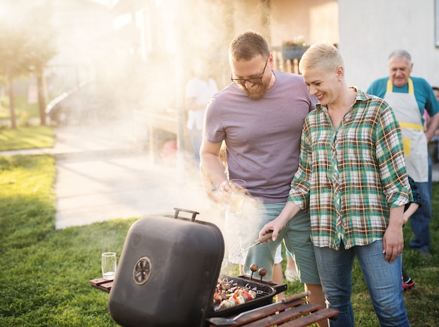Happy couple making barbeque for their family in their backyard.