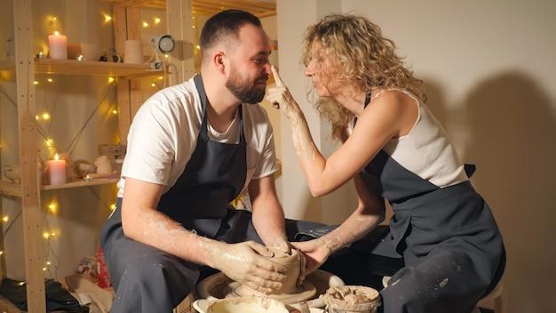 포터의 바퀴에 점토 주전자를 만드는 행복 한 커플. 소녀는 점토 작업장에서 더러운 손가락으로 남자의 코를 만지고 닫습니다