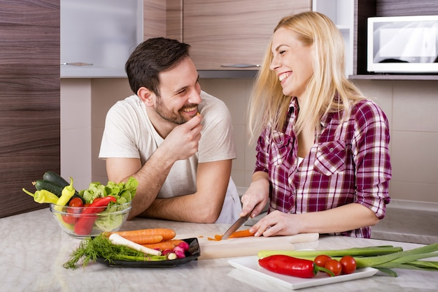 Happy couple making a fresh salad with vegetables on the kitchen counter