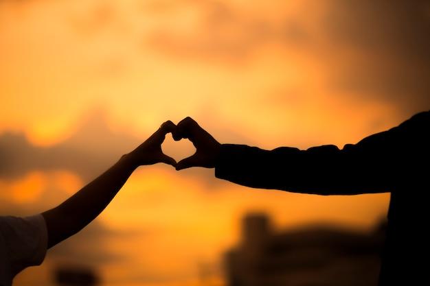 Happy couple making heart shape and sunset. love unique concept.