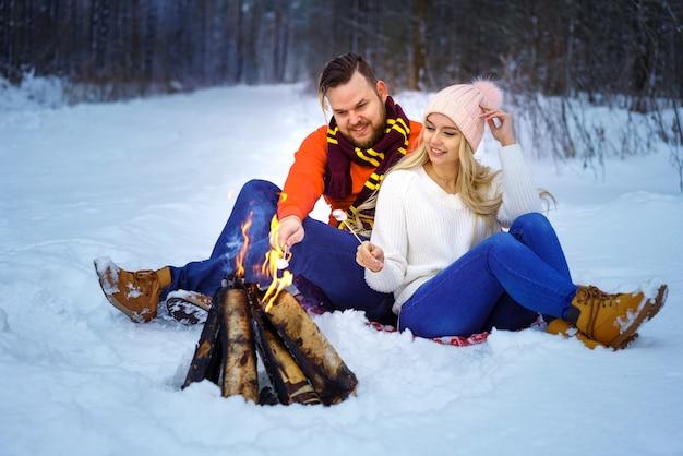 森の中で冬の幸せなカップルの男性と女性は、火のロマンチックなピクニックでマシュマロを揚げます
