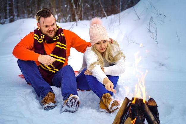 森の中で冬の幸せなカップルの男性と女性は火のロマンチックなピクニックでマシュマロを揚げる
