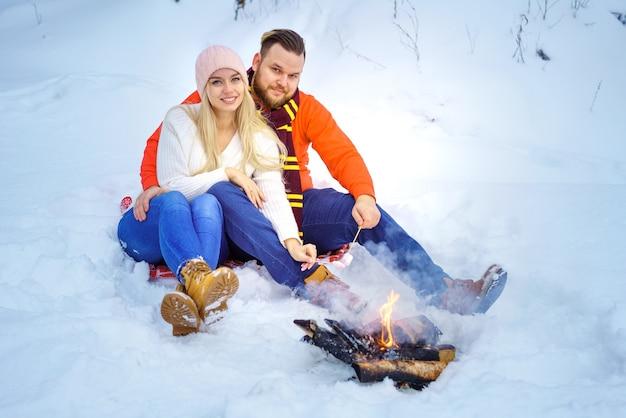 森の中で冬の幸せなカップルの男性と女性は火でマシュマロを揚げる