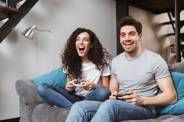 幸せなカップルの男性と女性が自宅のソファに座って、ジョイスティックと一緒にビデオゲームをプレイ