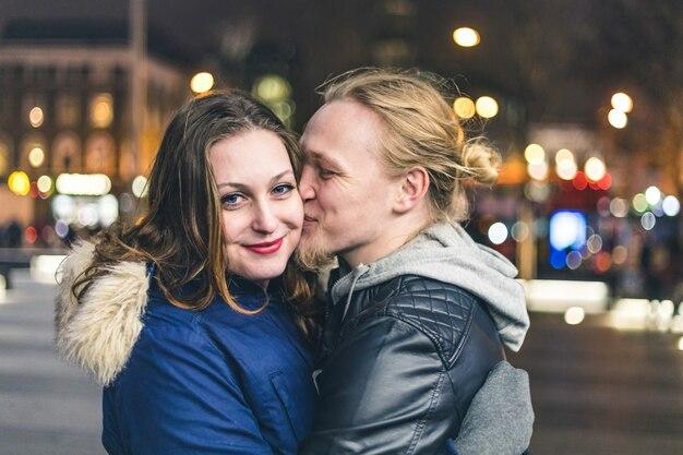 Happy couple, man kissing his girlfriend