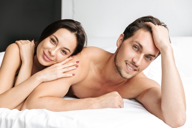 Happy couple man and woman hugging together, while lying in bed at home or hotel apartment