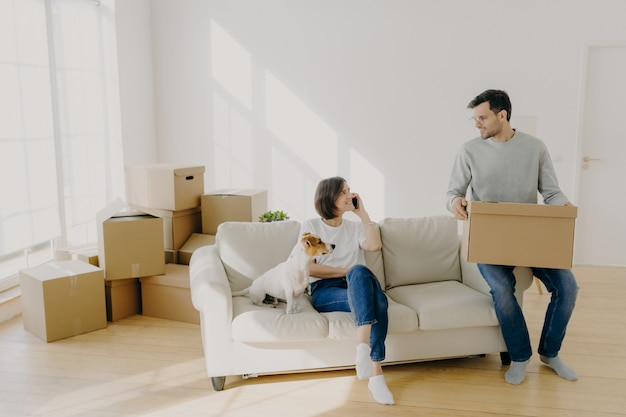 Happy couple move in new home, pose on sofa with pet and boxes