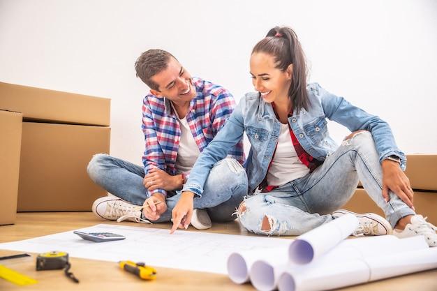 幸せなカップルは、インテリアデザインを計画している間、楽しんで新しい家に引っ越しました。