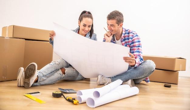 幸せなカップルは、青写真をめぐってインテリアデザインについて話し合う新しい家に引っ越しました。