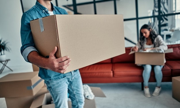 Happy couple moving into a new house and doing home renovations, they are carrying cardboard boxes.