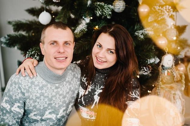Счастливая пара возле елки с рождеством и счастливыми праздниками