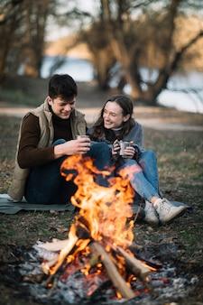 キャンプファイヤーの近くの幸せなカップル