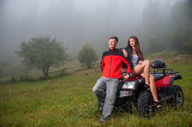 Happy couple near four-wheeler atv in foggy nature