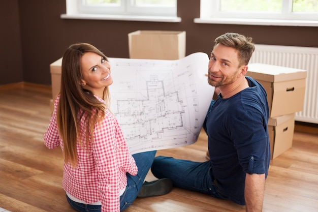 Happy couple in new apartment with blueprint