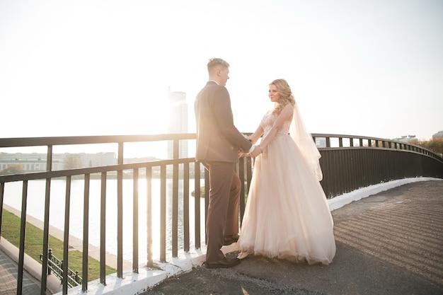 Счастливая пара молодоженов, стоя на мосту. фото с копией пространства