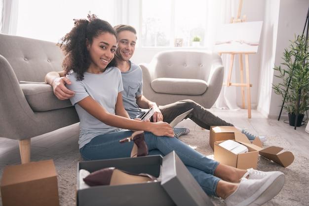 幸せなカップル。彼女とオンラインショッピングをしながら彼のガールフレンドの隣に座っている素敵なポジティブな男