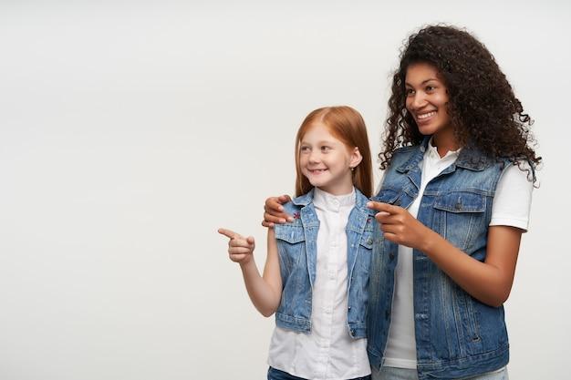 Счастливая пара очаровательных девушек в повседневной одежде показывает в сторону с поднятыми указательными пальцами и весело улыбается, будучи в хорошем настроении, позируя на белом