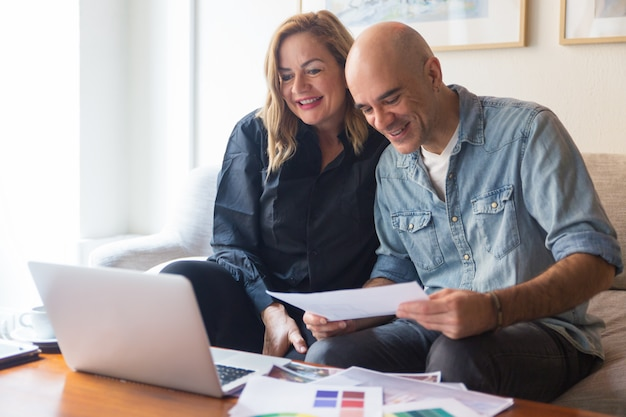 Счастливая пара клиентов разговаривает с дизайнером интерьера