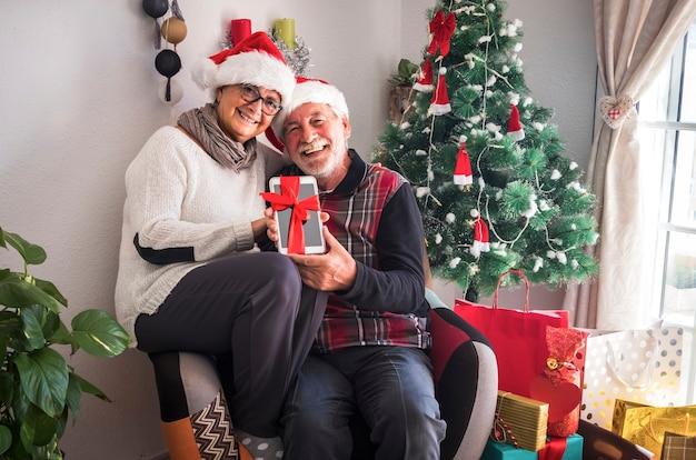 산타 모자를 쓰고 같은 안락의자에 함께 앉아 있는 행복한 노인 부부. 크리스마스 선물로 받은 태블릿을 들고. 백그라운드에서 선물과 크리스마스 트리