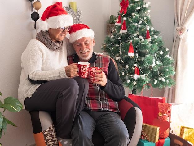 빨간 차 두 잔과 함께 같은 안락의자에 함께 앉아 있는 산타 모자를 쓴 행복한 노인 부부. 백그라운드에서 선물과 크리스마스 트리