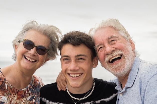 Счастливая пара бабушек и дедушек, обнимая подростка внука. красивые люди улыбаются беззаботно