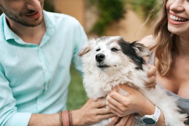 草の上の裏庭で犬と遊んでいる男の幸せなカップル。元気な老犬