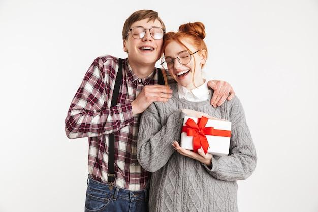 プレゼントボックスを与える学校のオタクの幸せなカップル