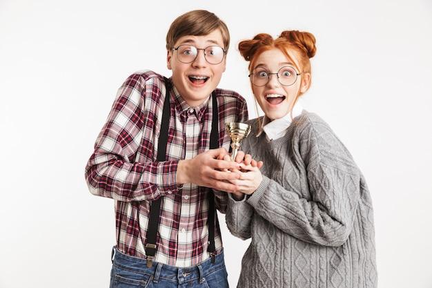 優勝トロフィーを保持している学校のオタクの幸せなカップル