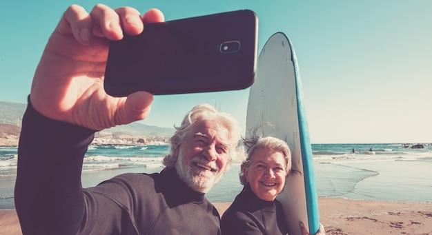 해변에서 행복한 커플이 서핑을 하고 함께 즐거운 시간을 보내고 있습니다.
