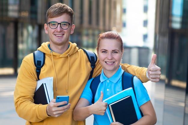 Счастливая пара студентов. мальчик и девочка с книгами, показывая большой палец вверх