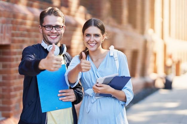 Счастливая пара студентов в кампусе учится на открытом воздухе
