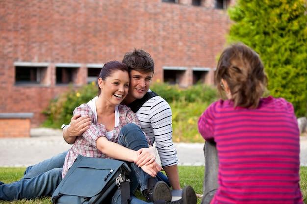 彼らの大学キャンパスで女性の友人と話す草の上に座っている学生の幸せなカップル