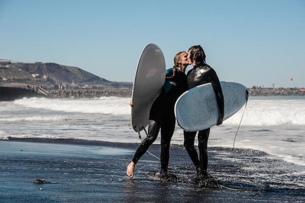Счастливая пара серферов в черных гидрокостюмах держит белую доску и целуется в воде на фоне неба и океана
