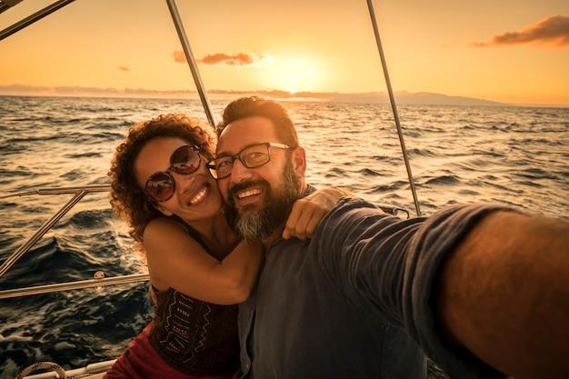 観光客の幸せなカップルは、休日の休暇で夏の日没を楽しんで自分撮りと笑顔を取ります-ヨットの贅沢なライフスタイルの人々-背景と青い海の日光