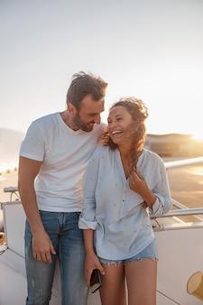 행복한 커플, 남자와 여자는 해질녘 비행기에 탑승할 준비를 하고 야외에 서서 흥분한 표정을 짓고 있습니다. 휴가, 라이프 스타일, 여행 개념