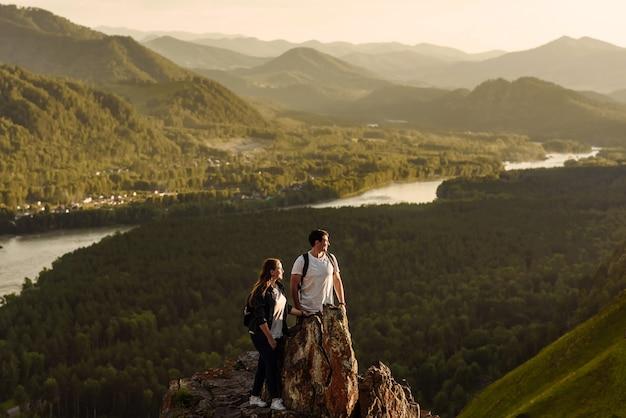 山頂のバックパックの勝者と観光客の男性と女性の幸せなカップル。