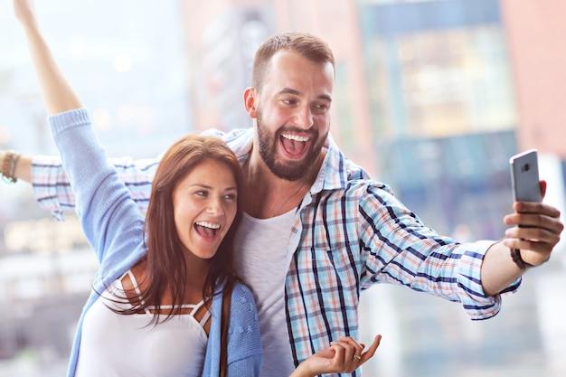 雨の日に街でスマートフォンを使用して観光客の幸せなカップル