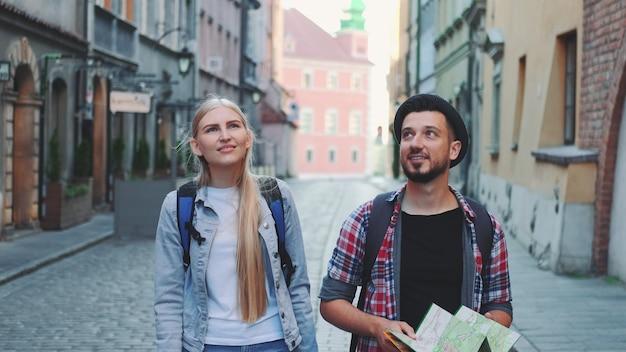 Счастливая пара туристов с картой, идущей по центральной улице старого европейского города. они смотрят вокруг и улыбаются.
