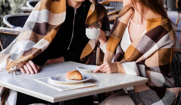 Счастливая пара жены и ее муж приют в пледе, разговаривают и пьют кофе. уютная и романтическая концепция любви. фото