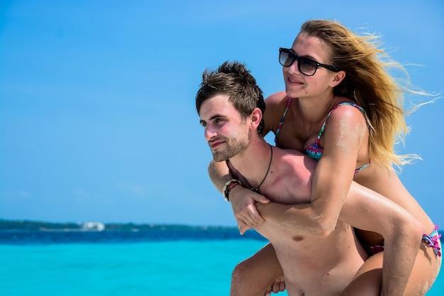ビーチで休暇中の若者の幸せなカップル