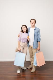 Счастливая пара молодых покупателей с бумажными пакетами и кредитной картой, стоя у стены изолированно в студии