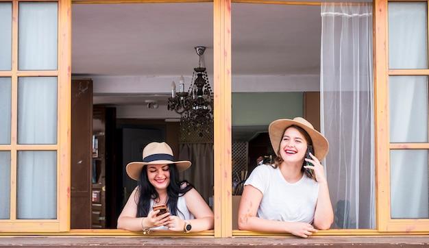 若い女性の白人の友人の幸せなカップルは、電話のインターネット接続を楽しんでバーの窓で一緒に楽しんでいます