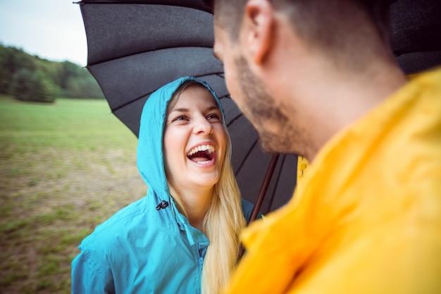 傘の下でハイキングで幸せなカップル
