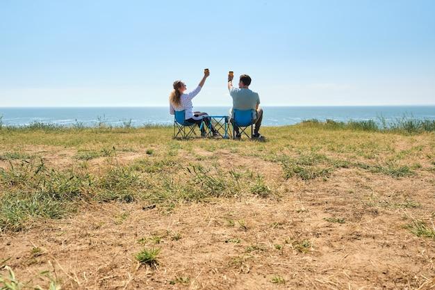 Счастливая пара на свидании любуется красивым пейзажем, сидя на стульях для путешествий. влюбленная пара. семейный отдых, отдых на территории кемпинга. счастливые люди вместе рядом, наслаждаясь природой